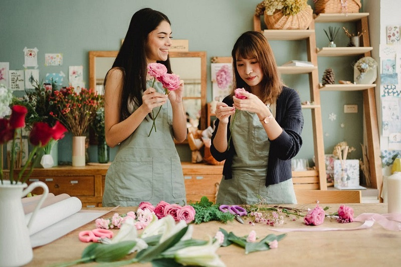 Diverse female coworkers preparing roses for floral decoration