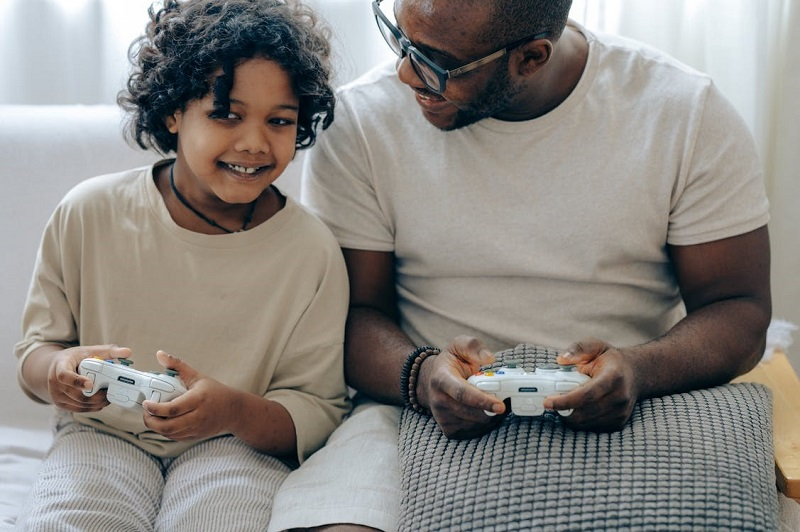 Happy black father and daughter playing video game with controllers