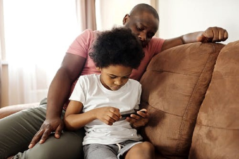 Father Looking at his Son Playing on a Smartphone