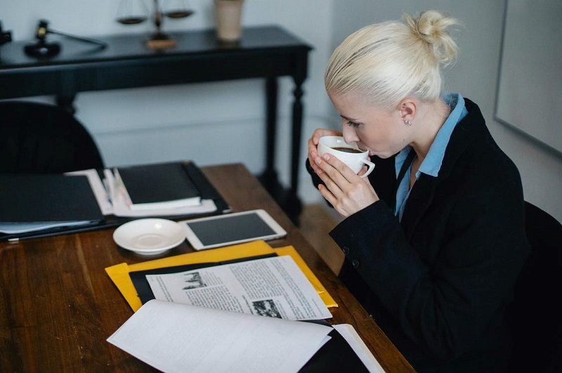 Focused young female lawyer drinking coffee while working on case in office