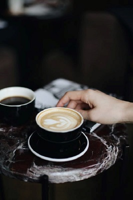 Person Holding A Cup Of Cappuccino