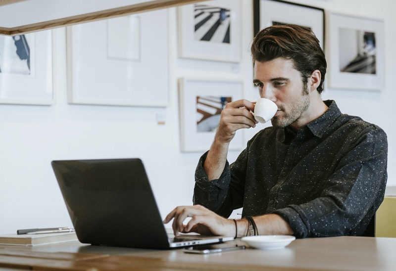 a man sits at a desk, using a laptop and drinking from a tea cup