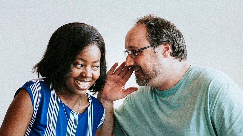 Man with a glasses whispering to his girl friend