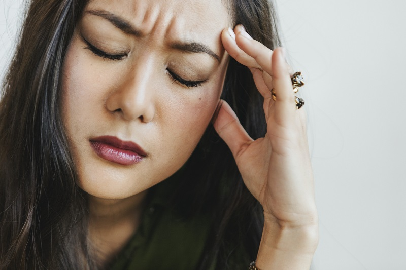 woman holding head and looking stressed experiencing HF bipolar disorder- try betterhelp online therapy