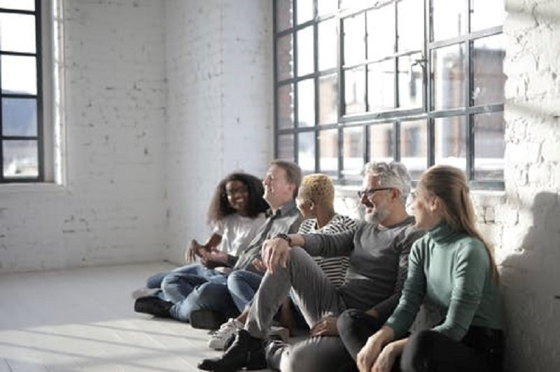 A Group Of People Sitting on The Floor Inside A Room