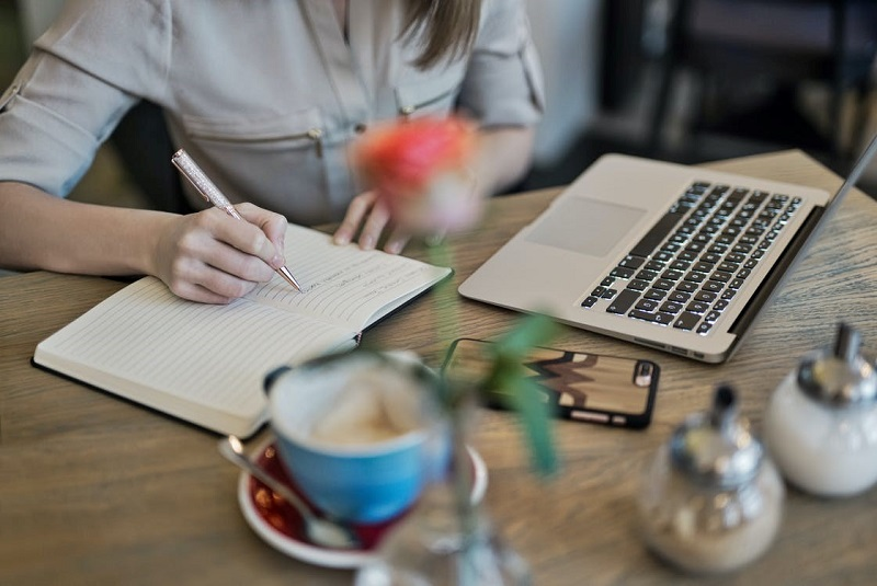 Person Writing On A Notebook Beside Macbook