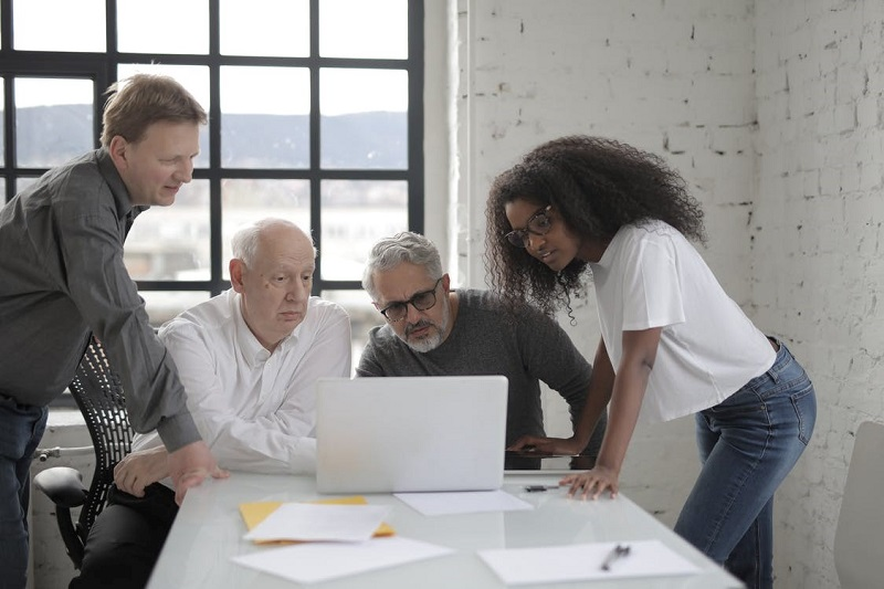 Group Of People Looking At A Laptop