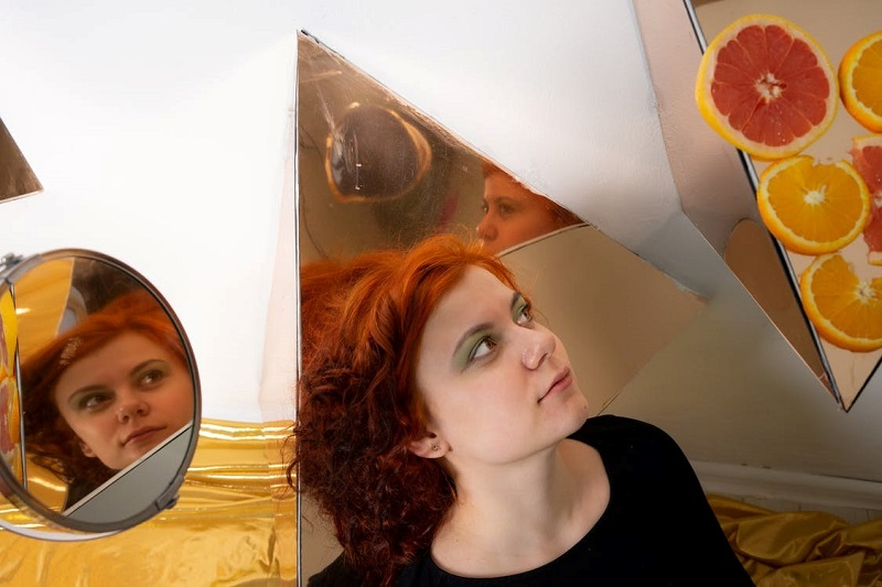 Redheaded woman surrounded by mirrors