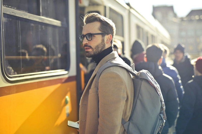 Man in Brown Coat and Gray Backpack Posing for a Photo