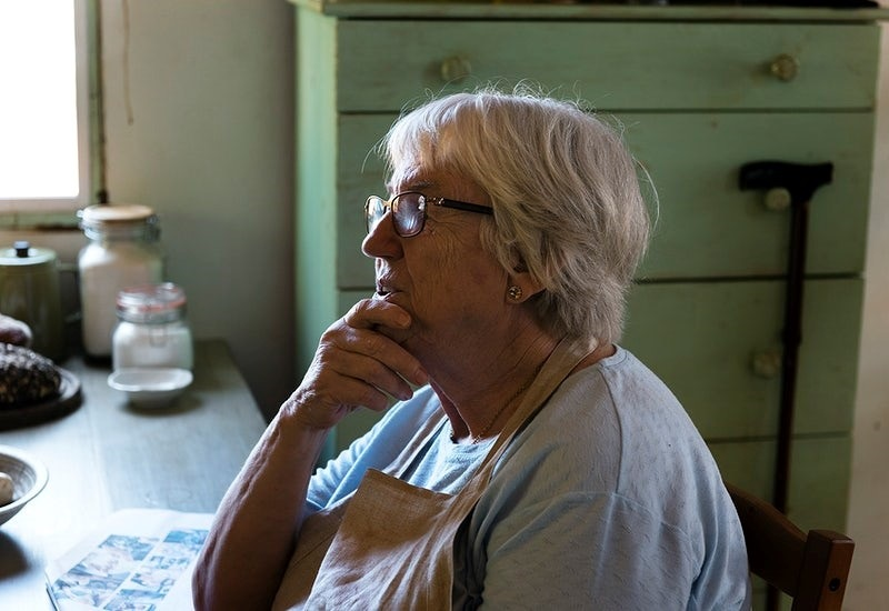Senior woman sitting alone in her kitchen