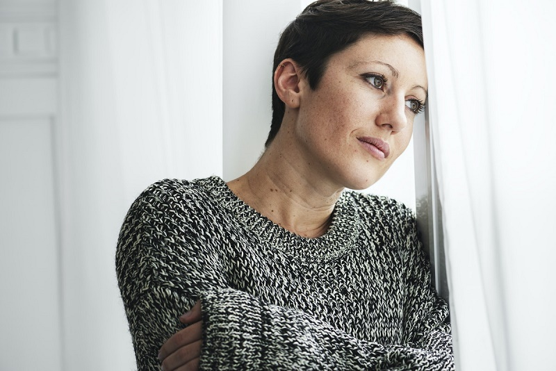 first therapy session - woman with short brown hair and wearing a grey sweater is staring out a window deep in thought - betterhelp online therapy article 2021