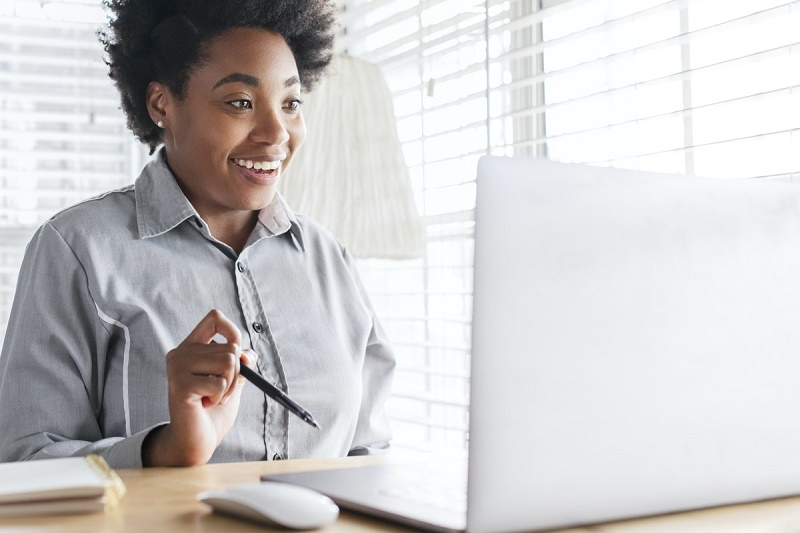 woman holding pen smiling while looking at her laptop on a video call with her therapist - betterhelp online therapies article 2021