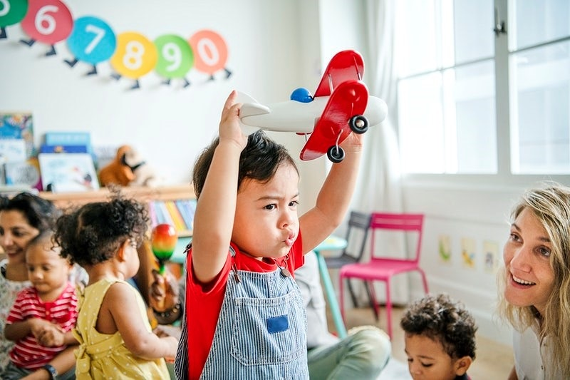 Preschooler enjoying playing with his airplane toy
