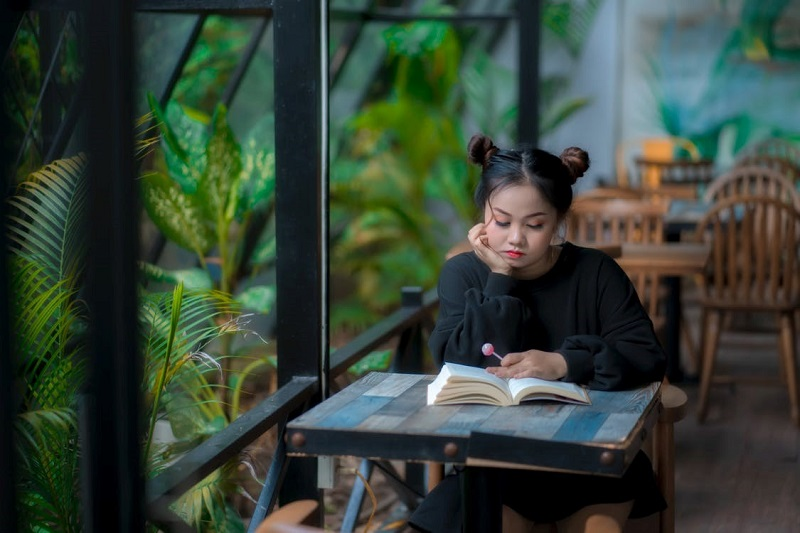 Serious young Asian lady reading book in cafeteria