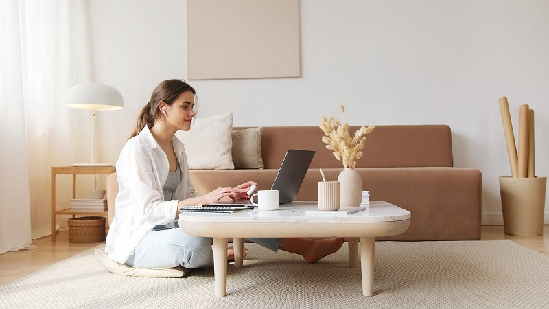 Content woman using laptop on floor