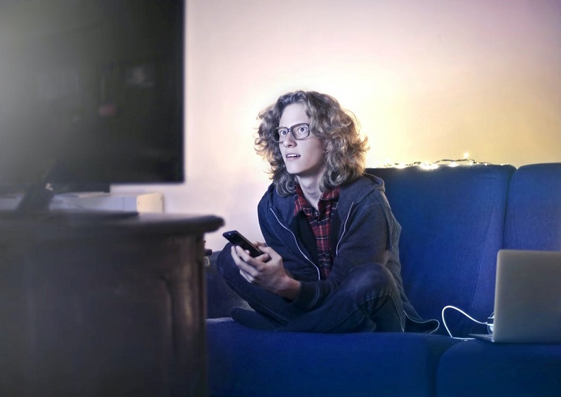 Young man using smartphone and watching TV in living room