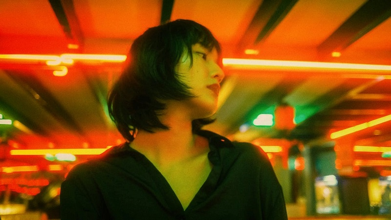 Thoughtful young ethnic woman in neon lights in cafe