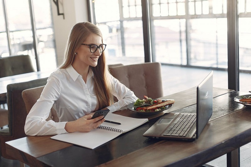 Young cheerful businesswoman using smartphone and laptop in cafe during lunch time