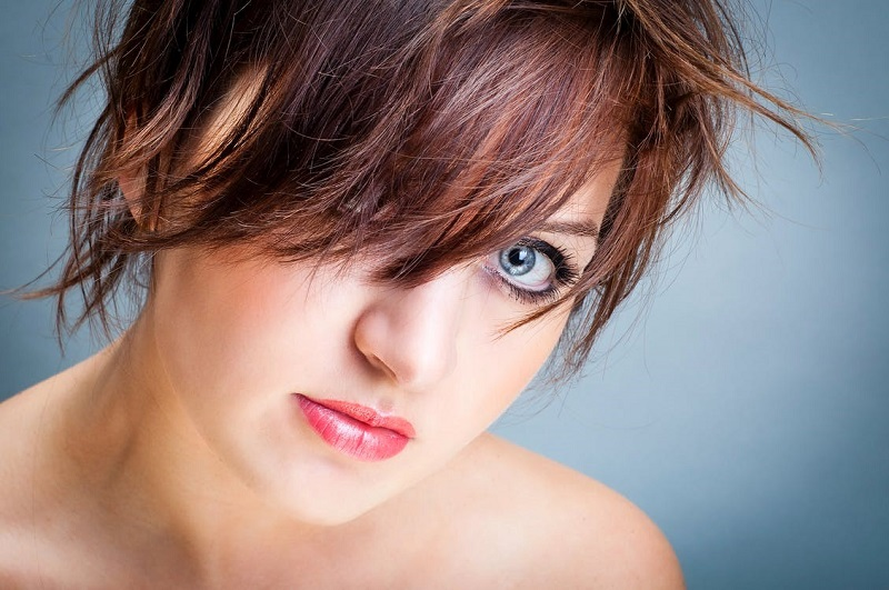 Bright woman with trendy hairstyle and bare shoulders