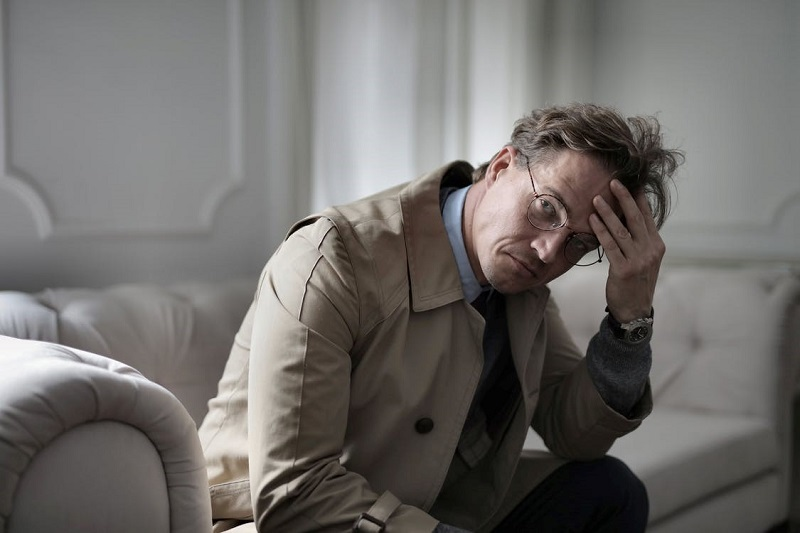 Thoughtful man in stylish outfit sitting on couch