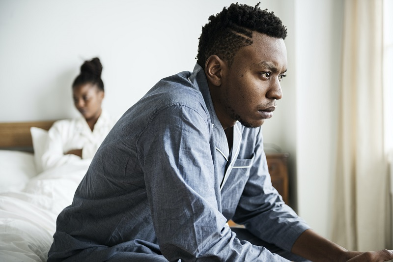 man looking stressed with woman in background