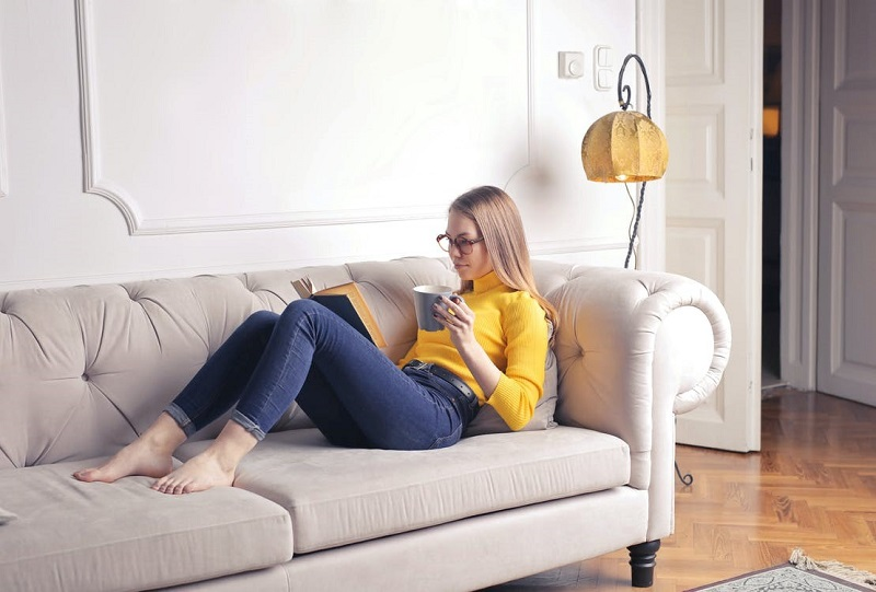 Woman Sitting on White Couch While Reading a Book
