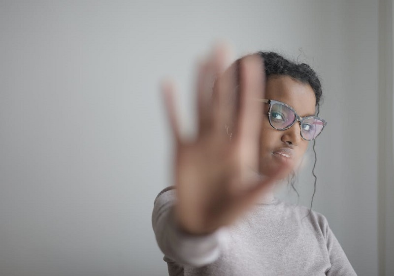 Ethnic woman doing stop gesture with palm at camera