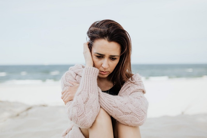 Woman in White Sweater Sitting on Beach