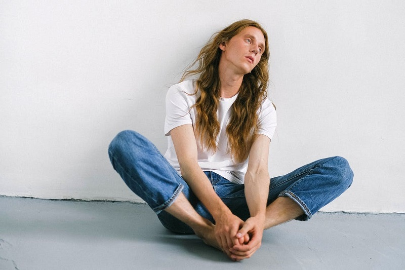 Woman in White Crew Neck T-shirt and Blue Denim Jeans Sitting on Floor