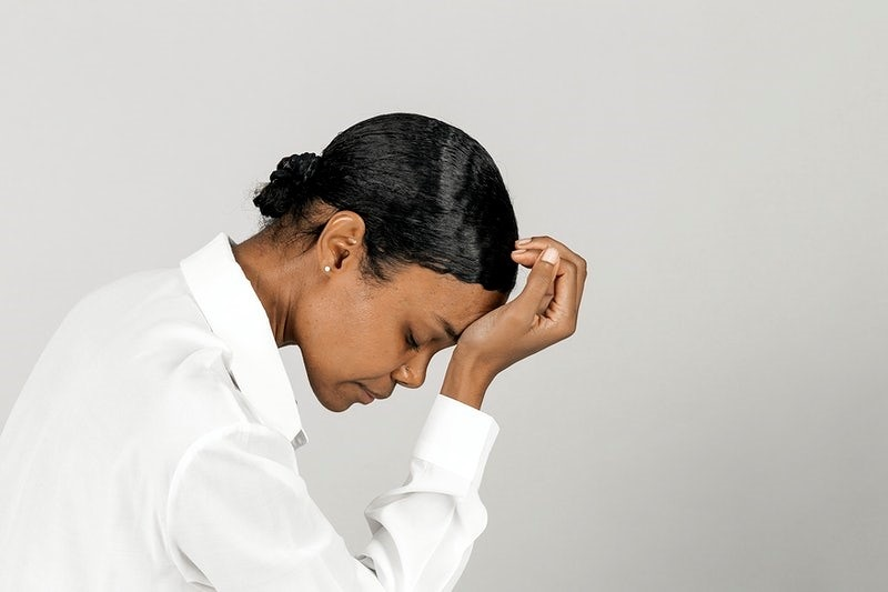 Unhappy black woman touching her head
