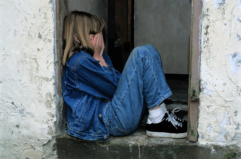 Girl Sits on Gray Concrete Surface
