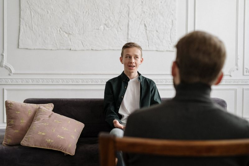 teen kid talking in a room on a couch and looking in distance - going to therapy can be scary at first but we can help