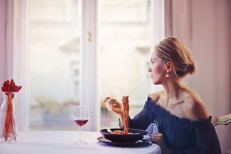 Woman Sitting on Chair While Eating Pasta Dish